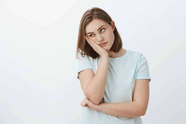 La ragazza odia frequentare lezioni noiose all'università con la faccia appoggiata a portata di mano roteando gli occhi dalla noia e dal fastidio in piedi indifferenti e scontenti sul muro grigio in maglietta alla moda Foto Gratuite
