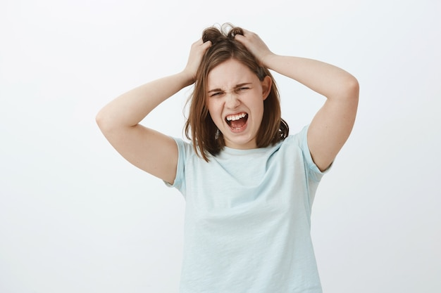 Girl hates think too much. displeased distressed young upset european woman with brown short haircut screaming while losing temper being angry or mad messing up or pulling hair out of head Free Photo