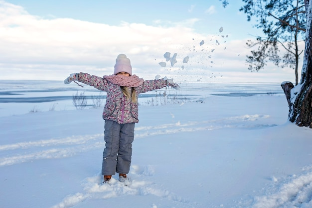 女の子は雪の降る冬の日に凍った湖で楽しんで、季節の野外活動、ライフスタイル Premium写真