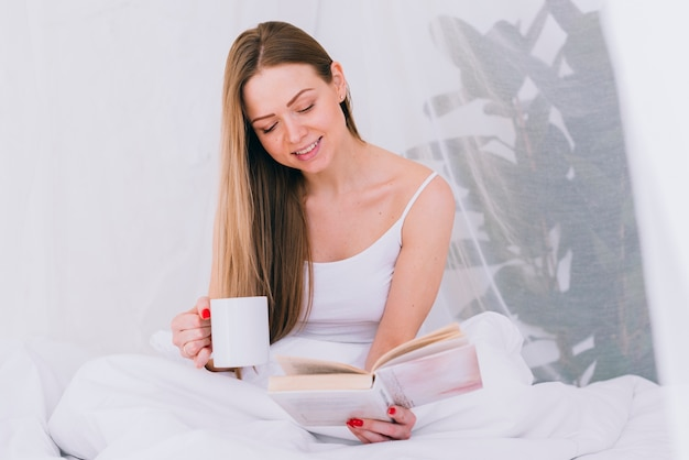 Girl having coffee with a book on the bed Free Photo