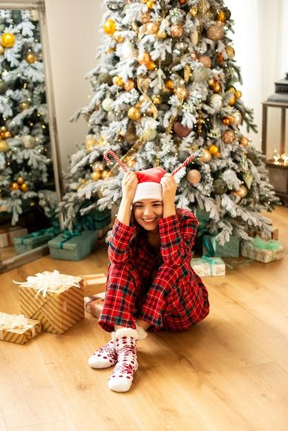 재미와 크리스마스를 축하하는 소녀. 배경에 선물 크리스마스 트리 장식. 프리미엄 사진