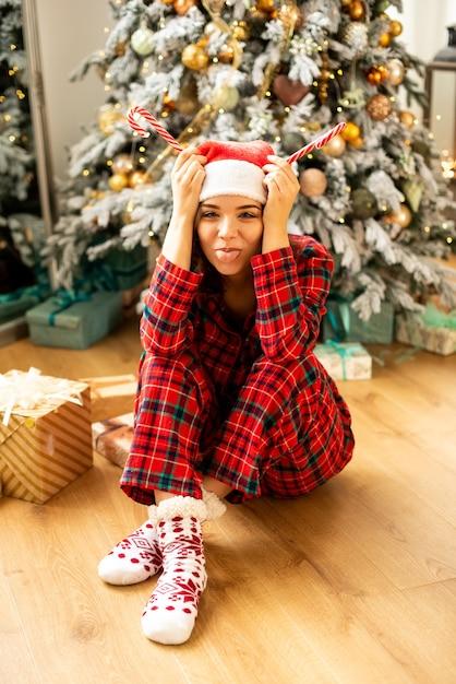 재미와 크리스마스를 축하하는 소녀. 그녀는 웃음으로 혀를 보여줍니다. 배경에 선물 크리스마스 트리 장식. 프리미엄 사진