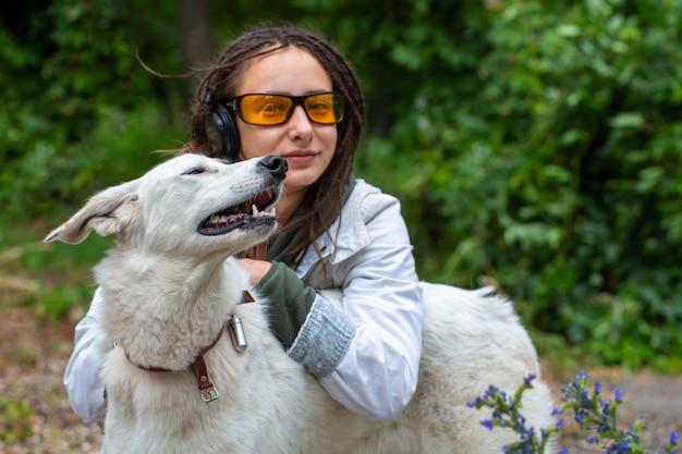 Girl in headphones and glasses hugs a dog. Premium Photo