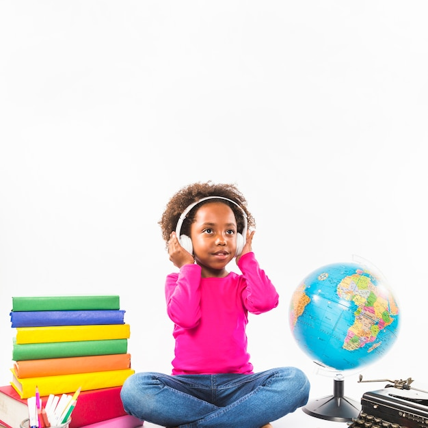 Girl in headphones near books and globe in studio Free Photo