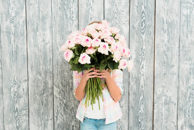 Girl hiding face by bouquet of roses Free Photo