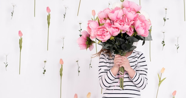 Girl hiding behind rose bouquet Free Photo