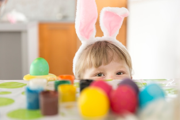 Girl hiding at table with easter eggs Free Photo