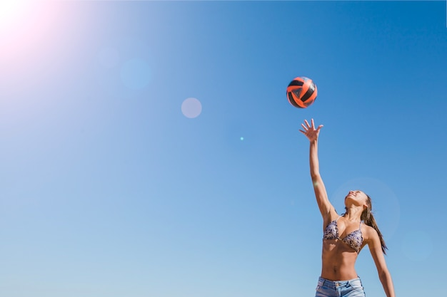 Girl hitting volleyball on a sunny day Free Photo