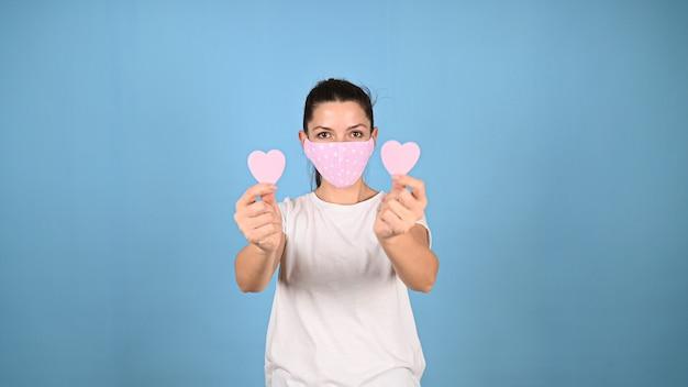 Девушка держит сердце руками в маске. фото высокого качества Premium Фотографии