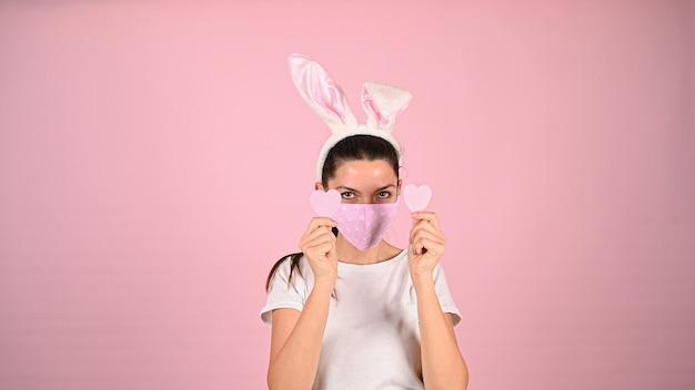 Девушка держит сердце руками в маске на розовом фоне. фото высокого качества Premium Фотографии