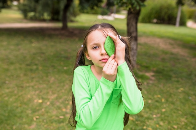 Girl holding artificial green leaf on her left eye standing on grass Free Photo
