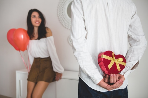 Girl holding balloons with heart shape while her boyfriend has a gift for her to the back Free Photo