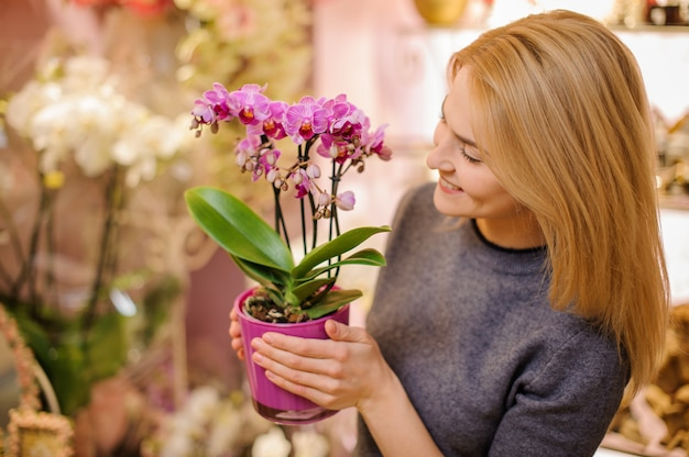 Girl holding a beautiful pink orchid in pot Premium Photo
