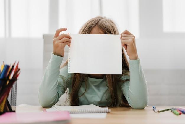 Ragazza che tiene una carta bianca davanti a lei Foto Gratuite