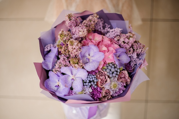 Girl holding a bouquet of tender lilac and orachids, and other spring flowers Premium Photo