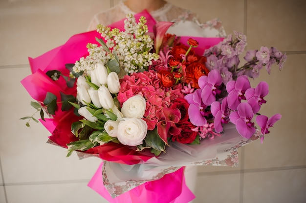 Girl holding a bouquet of white tulips and lilac, pink orchids and hydrangeas and red roses Premium Photo