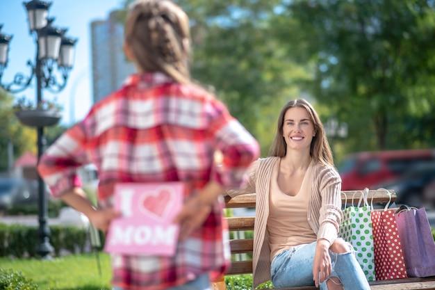 공원 벤치에 앉아 그녀의 웃는 엄마 카드를 들고 소녀 프리미엄 사진
