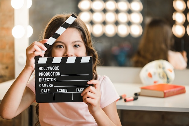 Girl holding clapperboard in front of her mouth Free Photo