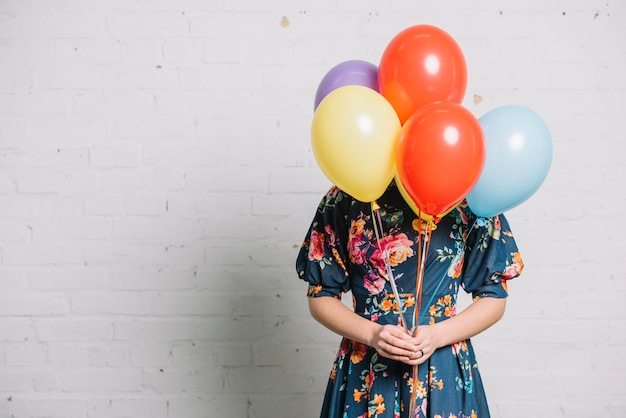 Girl holding colorful balloons in front of her face standing against wall Free Photo