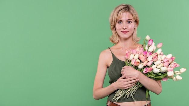 Girl holding flowers and looking at photographer Free Photo