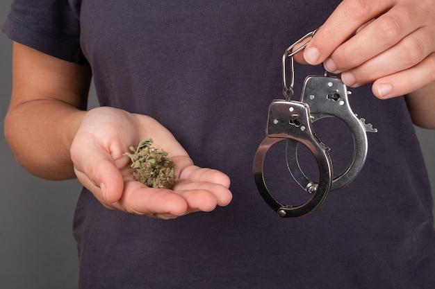 Girl holding in hand a bud of marijuana and handcuffs Premium Photo