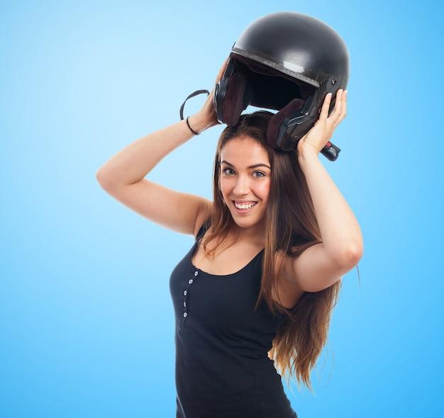 Girl holding helmet over head Free Photo