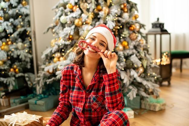새해 캐러멜에서 뿔을 잡고 크리스마스를 축하하는 소녀. 배경에 선물 크리스마스 트리 장식. 프리미엄 사진
