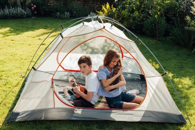 Girl holding little dog sitting with her brother in tent camp in park Free Photo
