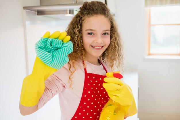 Girl holding napkin and spray bottle in kitchen Free Photo