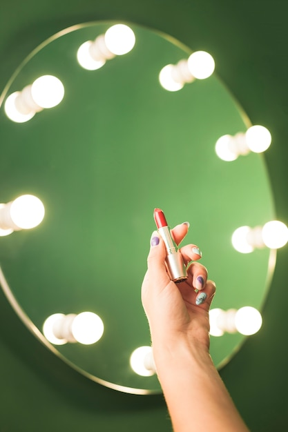Girl holding red lipstick in front of a mirror Free Photo