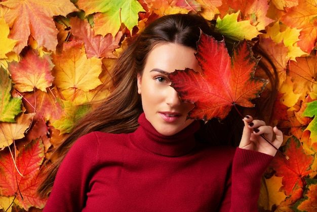 Girl holding red maple leaf in hand over colorful fallen leaves background. gold cozy autumn concept. Premium Photo