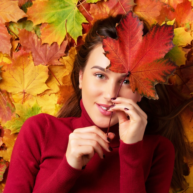 Girl holding red maple leaf in hand over colorful fallen leaves background. Premium Photo