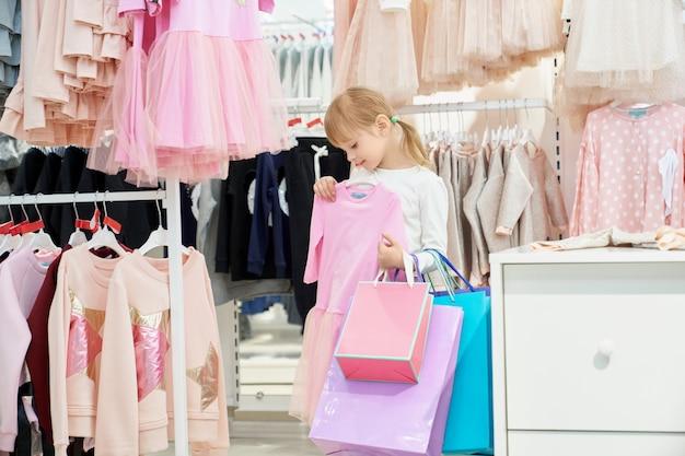 쇼핑백을 들고 핑크 드레스를 선택하는 여자. 무료 사진
