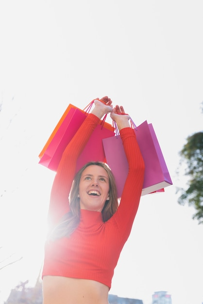 Girl holding shopping bags above her head Free Photo