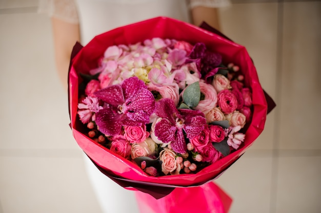 Girl holding a spring bouquet of tender pink and crimson flowers Premium Photo