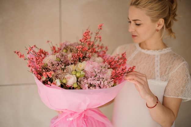 Girl holding a spring bouquet of tender rose color and white flowers Premium Photo