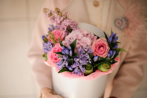 Girl holding a spring box of tender pink and violet flowers Premium Photo