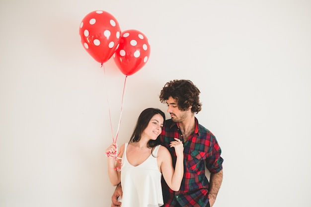 Girl holding two balloons as she rests her head on her boyfriend's chest Free Photo