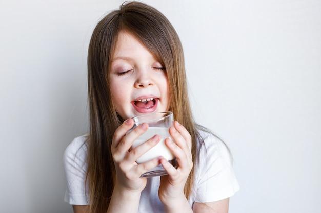 Девушка держит стакан молока и наслаждается вкусом пространство для текста Premium Фотографии