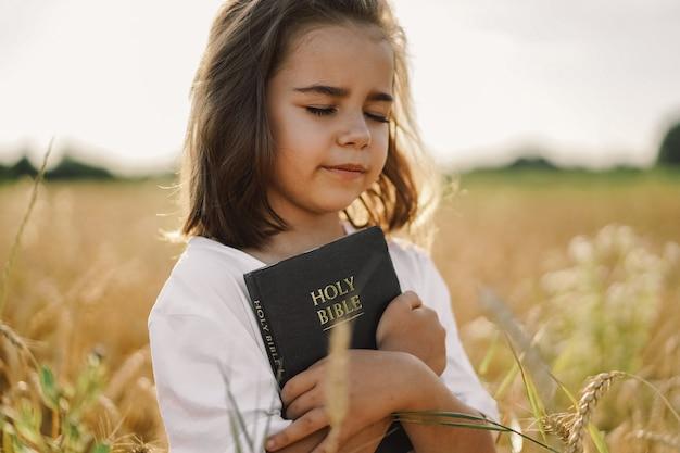 女の子は彼女の手で聖書を保持しています。フィールドで聖書を読む。信仰、霊性、宗教のコンセプト。平和、希望 Premium写真