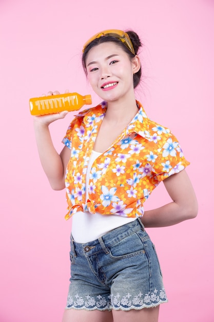 The girl holds a bottle of orange juice on a pink background. Free Photo