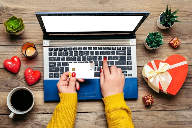 Girl holds debit card, chooses gifts, makes purchase, laptop, coffee cup, two hearts, bag on wooden table Premium Photo