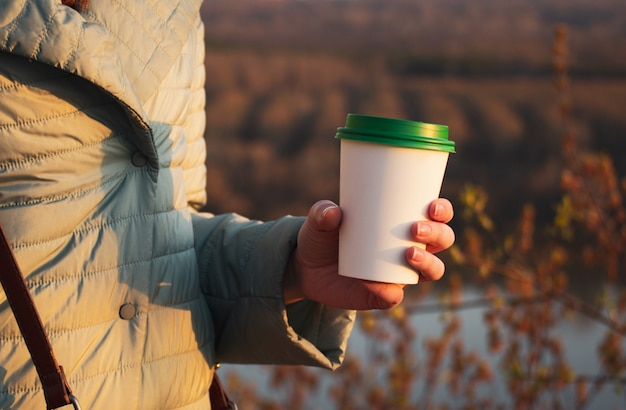 The girl holds in her hand a paper cup for coffee. free space for text Premium Photo