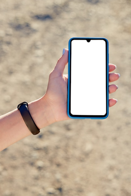 Girl holds a mobile phone on vacation in nature. mockup Premium Photo