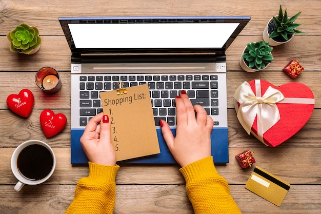 Girl holds shopping list, debit card, chooses gifts, makes purchase, laptop, coffee cup Premium Photo
