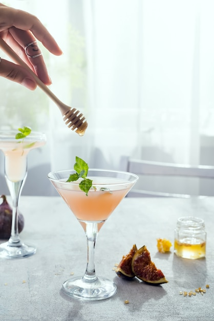 Girl holds a stick over exotic cocktail Premium Photo