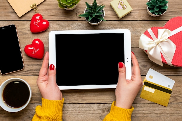 Girl holds tablet, debit card, chooses gifts, makes purchase, coffee cup, two hearts, bag on wooden table Premium Photo