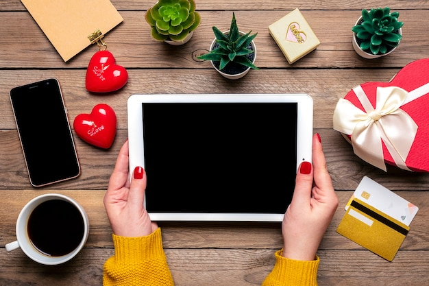 Girl holds tablet, debit card, chooses gifts, makes purchase, coffee cup, two hearts Premium Photo