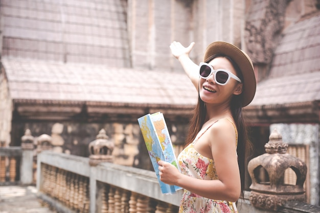 Girl holds a tourist map in the old town. Free Photo