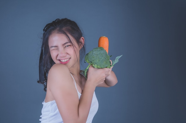 Girl holds the vegetables on a gray background. Free Photo